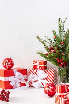 선물 상자와 빨간 공, 전나무 나뭇가지, 산사나무 가지, 흰 벽 배경, 새해, 크리스마스 컨셉의 꽃병