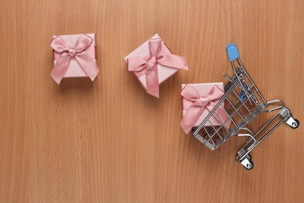 オフィスデスクのギフトボックスとショッピングカート。ショッピングのコンセプト、休日、誕生日。