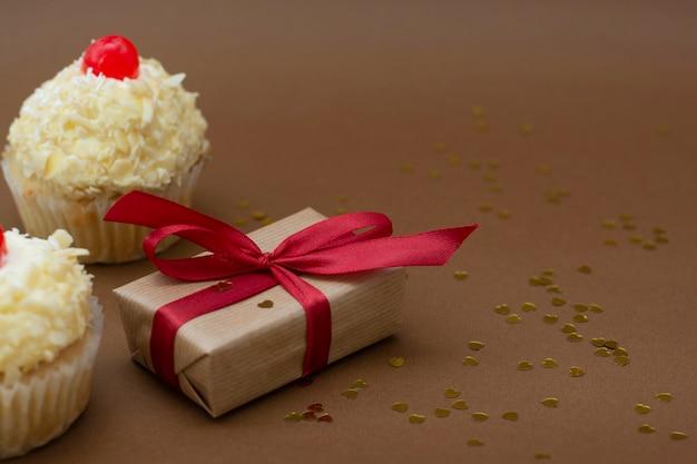 チェリーを上に乗せたギフトボックスとバニラカップケーキ。誕生日のコンセプト。テキスト用のコピースペースが付いた甘いデザート。