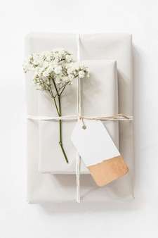 Gift boxes and baby's-breath flower twig tied together with string and tag