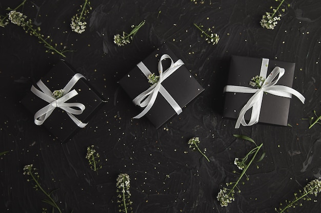 Gift boxes in black and white color with flowers. wrapping modern