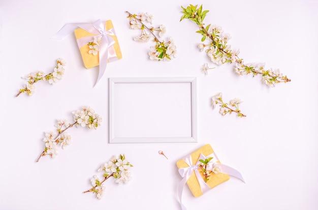 ギフトボックス、コピースペースのある白い背景にテキストのフレームが付いた開花桜の枝。フラットレイ、3月8日、母の日、バナー。上面図
