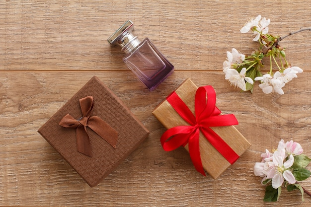 Gift boxes, a bottle of perfume with flowering branches of cherry and apple trees on the wooden surface