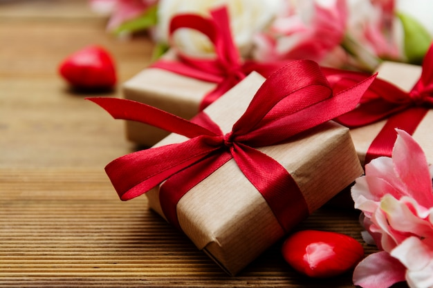 Gift boxes and bouquet of flowers on wooden background with copy space. valentine's day, love.