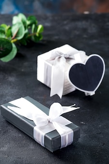 Gift boxes and chalkboard in the shape of heart with green plant twig on a dark stone background.