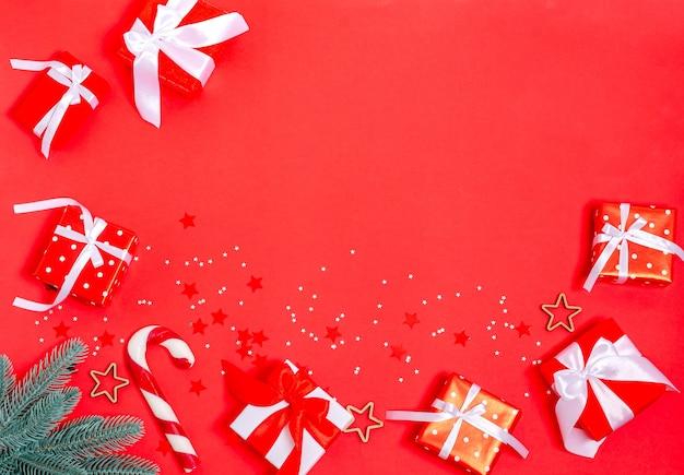 ギフトボックス、クリスマスのおもちゃ、モミの枝、星、赤い背景のキャラメル杖。バナー、はがきフォーム。コピースペース、フラットレイ。年末年始、クリスマス、休日、2021年上からの眺め