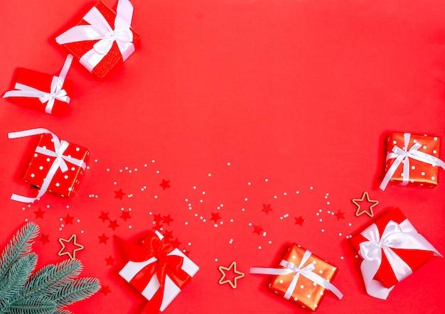 赤い背景の上のギフトボックス、クリスマスのおもちゃ、モミの枝、星。バナー、はがき空白。コピースペース、フラットレイ。年末年始、クリスマス、休日2021年の上面図