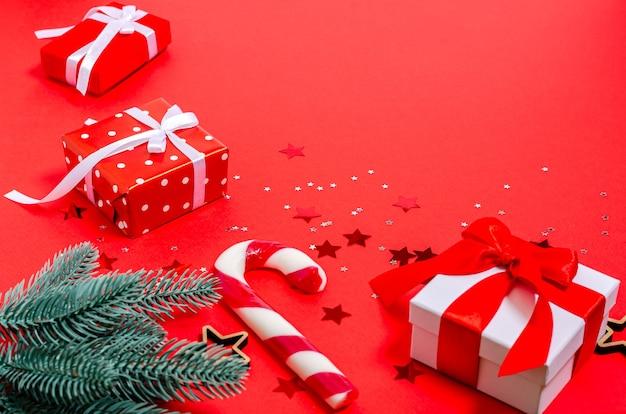 ギフトボックス、クリスマスのおもちゃ、モミの枝、木の星、赤い背景のキャラメルの杖。バナー、はがきフォーム。コピースペース、フラットレイ。正月、クリスマス、休日、2021年。上からの眺め。