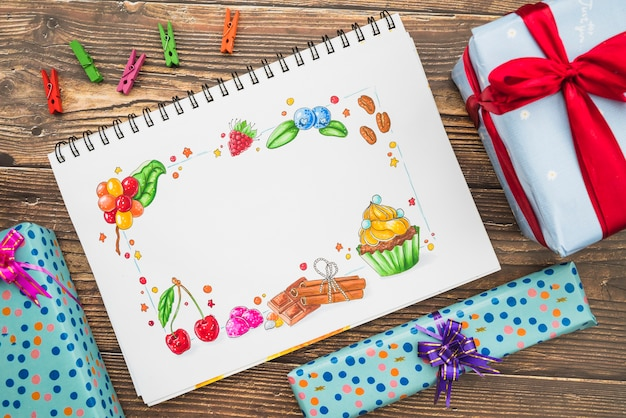 Gift boxes; clothespins and drawing on spiral notebook on wooden background