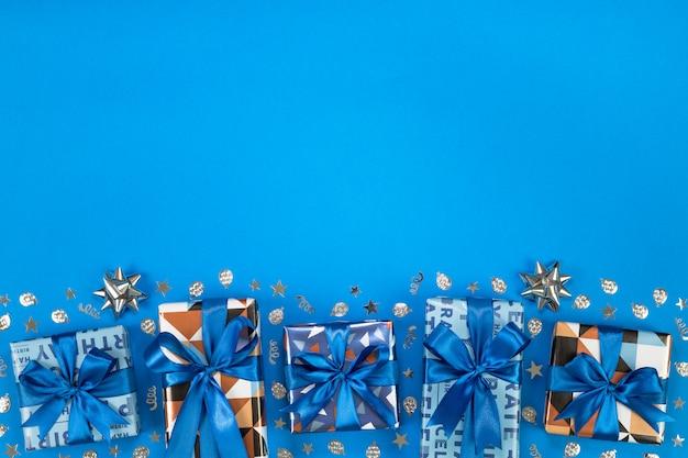 青い背景にギフトボックスの組成。フラットなテキストスペース。