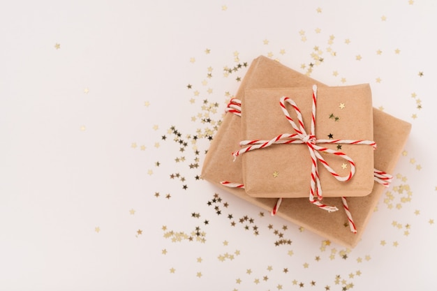 Gift boxes in craft paper with white-red new year's ribbon and gold stars on a beige background
