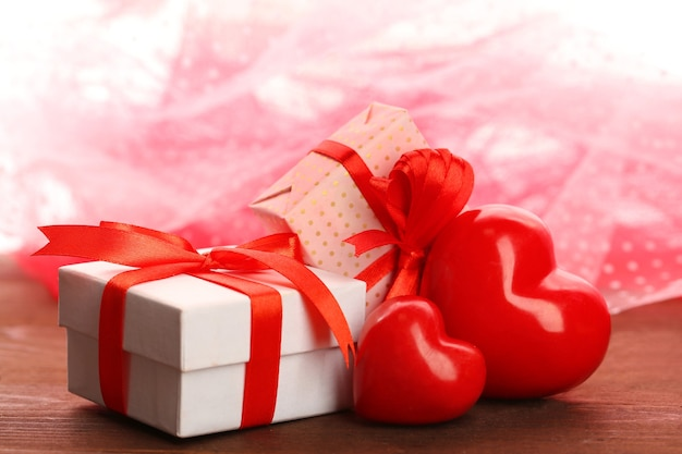 Gift boxes and decorative hearts on wooden table