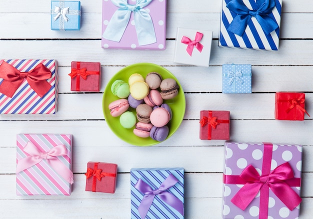 Gift boxes and french macaron on white wooden background