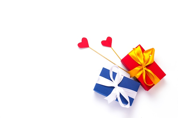 Gift boxes and hearts on sticks on a white background.