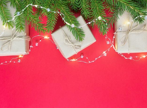 Подарочные коробки из крафт-бумаги с еловыми ветками и гирляндой на красном фоне. экологичная рождественская концепция.
