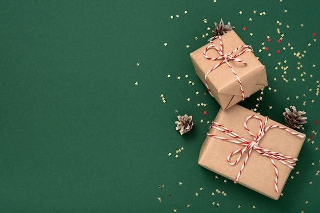 Подарочные коробки в крафт-бумаге с бело-красной новогодней лентой и золотыми звездами конфетти, шишки на зеленом фоне копируют пространство. рождество