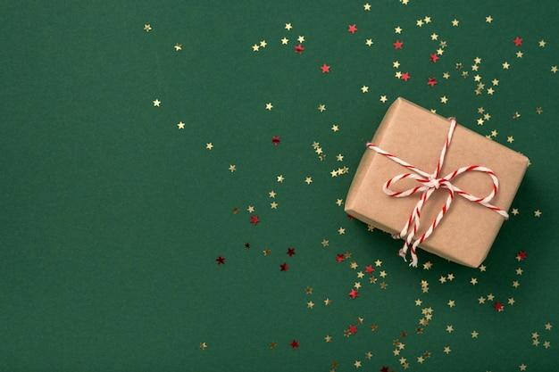 Подарочные коробки из крафт-бумаги с бело-красной новогодней лентой и золотыми звездами конфетти