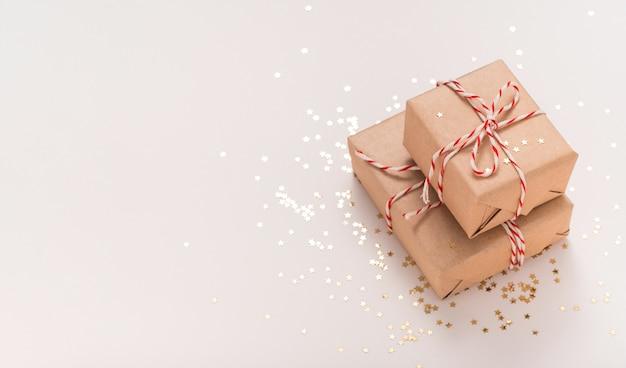 Подарочные коробки из крафт-бумаги с бело-красной новогодней лентой и золотыми звездами на бежевом фоне