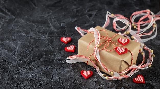 Подарочные коробки из крафт-бумаги, декоративная лента с деревянными сердечками и декоративные сердечки из фетра. день святого валентина. плоская планировка. вид сверху.