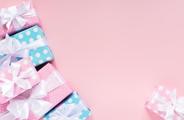 분홍색 배경에 흰색 리본과 활이있는 물방울 무늬의 선물 상자