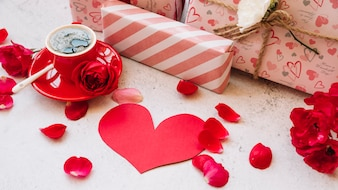 Gift boxes in wrap near flower petals, paper heart and cup with drink