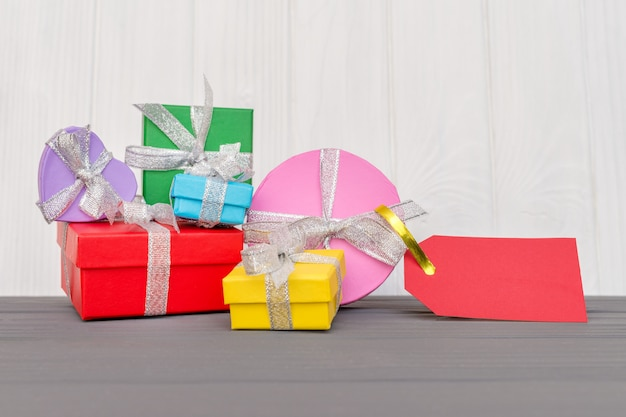 Gift boxes is tied with a ribbon with words boxing day and red tag on wood white surface