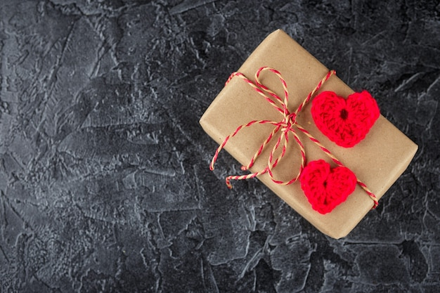 Gift boxes in kraft paper and decorative crocheted hearts. valentine's dayflat lay. top view.