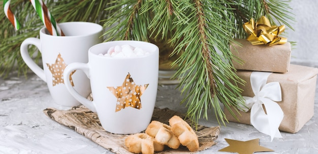 Gift boxes, mug with drink decorated with marshmallow and star shape cookies near evergreen christmas tree branches