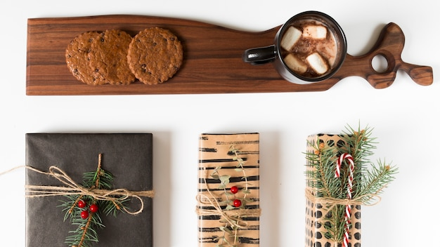 Gift boxes near wooden board with cocoa and cookies