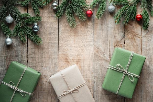Подарочные коробки на новогоднем фоне с ветвями сосны и рождественскими шарами, новогодним и рождественским праздничным фоном с копией пространства