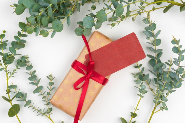 Gift boxes packed in craft paper with simple decor of green plant branches