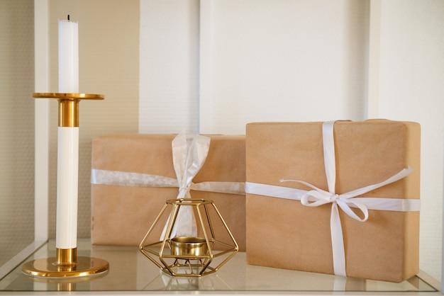 Подарочные коробки упакованные крафт-бумагой с белым бантом на полке с подсвечником