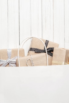 Gift boxes in paper bag on a white background, top view