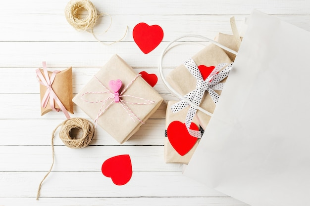 Gift boxes, paper cut heart and shopping bag on a white wooden background. valentine's day decorations