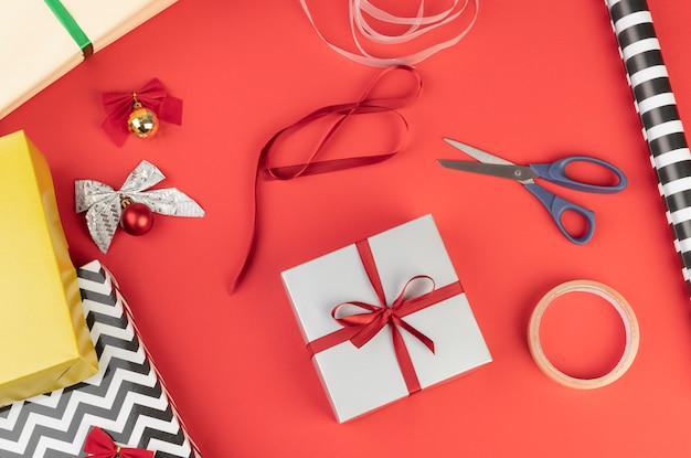 Gift boxes, paper, scisors, tape and christmas balls over red surface