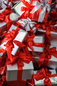 Подарочные коробки сложены в кучу. гора рождественских подарков крупным планом.
