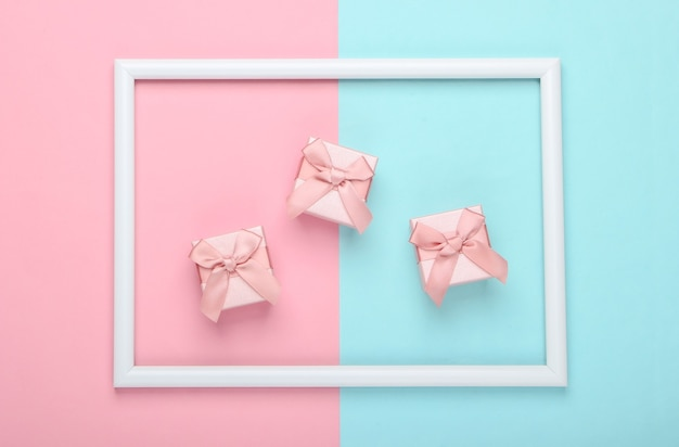 Gift boxes on pink blue pastel surface with white frame