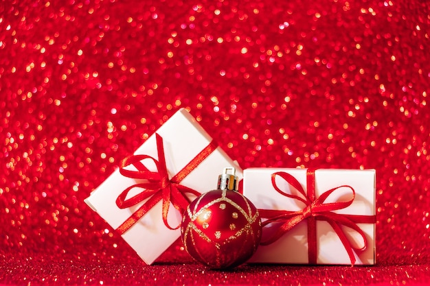 Gift boxes on a red glittering background. christmas concept, place for text.
