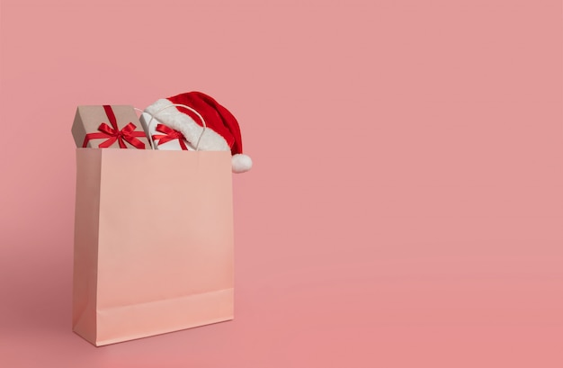 Gift boxes and santa claus hat in paper shopping bag.