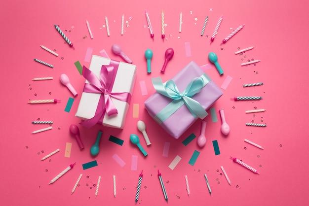 Scatole regalo circondate da candele e palloncini
