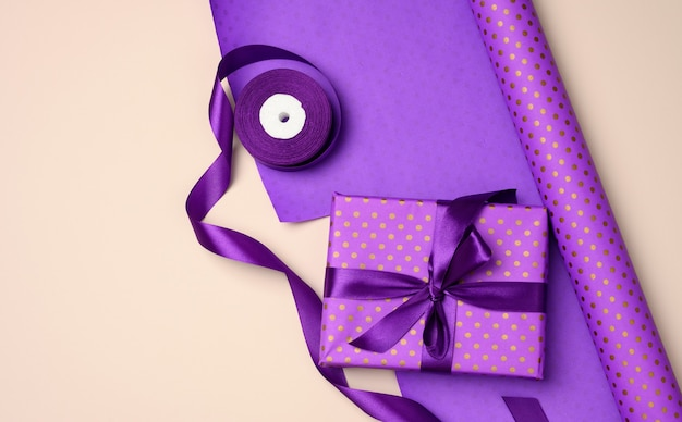 Gift boxes tied with purple silk ribbon on an beige background, top view. festive backdrop, flat lay