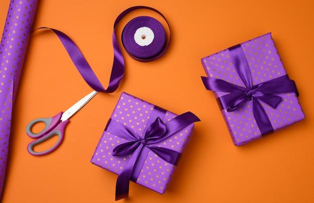 オレンジ色の背景、上面図に紫色のシルクリボンで結ばれたギフトボックス。お祝いの背景、フラットレイ
