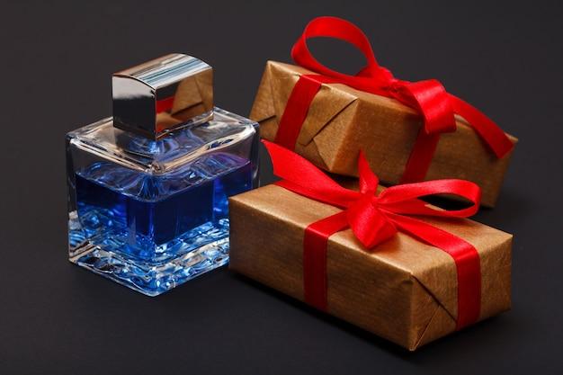Подарочные коробки, перевязанные красной лентой и флакон духов на черном фоне. концепция день празднования.
