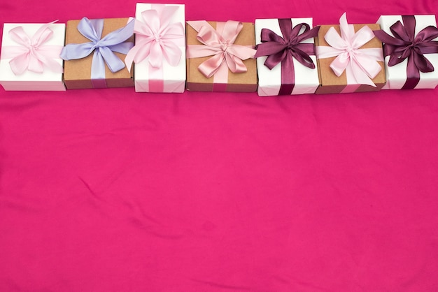 Gift boxes tied with satin colored ribbon pink background