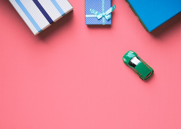 Gift boxes and toy car on pink