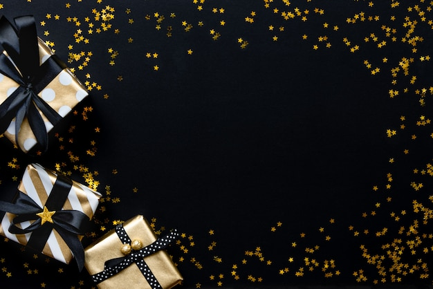 Gift boxes in various gold pattern wrapping papers over star shaped golden sequins on a black background.