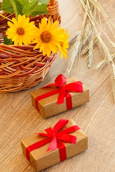 Gift boxes, whicker basket with flowers and spikelets of wheat on wooden boards. top view.