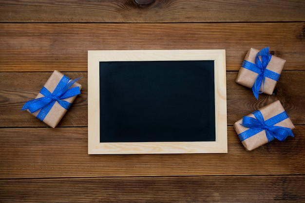Gift boxes with blue ribbon and empty chalkboard on wooden table. top view.