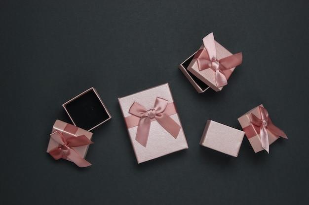Подарочные коробки с бантом на черном фоне. композиция на рождество, черную пятницу, день рождения или свадьбу.