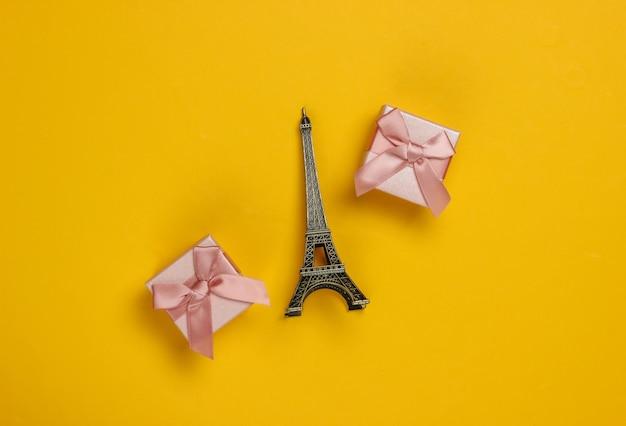 Подарочные коробки с бантами и статуэткой эйфелевой башни на желтом фоне. шоппинг в париже, сувениры